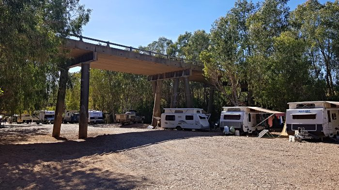 Campers under the bridge and at the river's edge