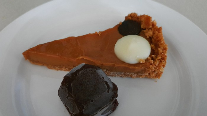 Caramel Tart served with a piece of homemade chocolate